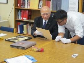 デルノア・ペーパーを見る深堀氏と、長崎原爆資料館の奥野正太郎氏